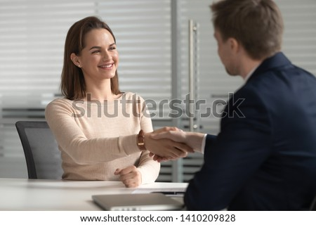 Happy successful female job applicant get hired employed at job interview negotiations, smiling manager candidate handshake hr customer make business deal with client, recruit and employment concept