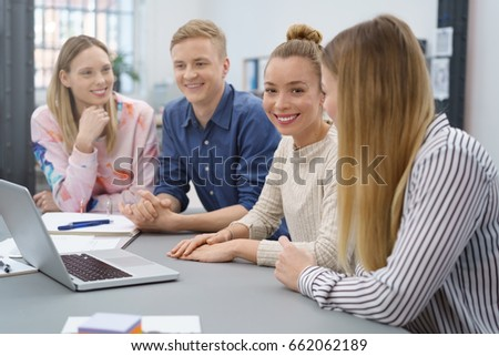 Happy successful female team leader in a meeting with her business colleagues looking at the camera with a beaming smile