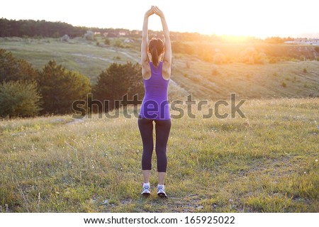 Happy successful sportswoman raising arms to the sky on golden back lighting sunset summer.
