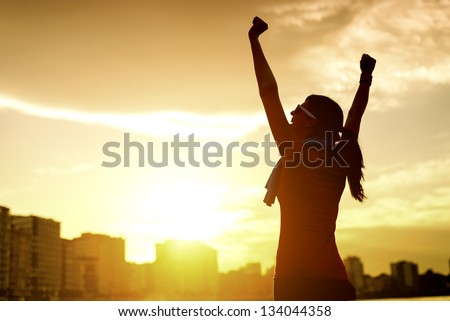 Happy successful sportswoman raising arms to the sky on golden back lighting sunset summer. Fitness athlete with arms up celebrating goals after sport exercising and working out outdoors. Copy space.