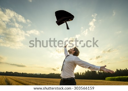 Happy Successful Young Businessman Throwing His Coat in the Air for being Free of Something with Wide Open Arms at the Field During Sunset.