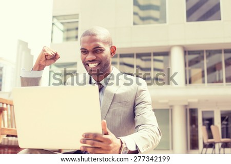 Happy successful young man with laptop computer celebrates success outside corporate office