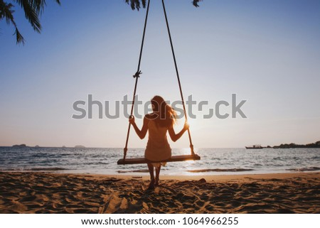 happy summer beach holidays, beautiful girl relaxing on swing at sunny sunset, enjoy getaway travel vacation at sea, happiness concept #1064966255