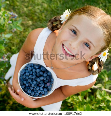 Happy summer - Lovely girl with fresh blueberries in the garden