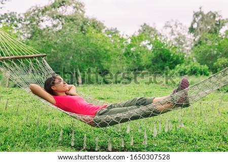 Happy summer relaxation woman sleeping in home backyard hammock relax enjoying retreat.