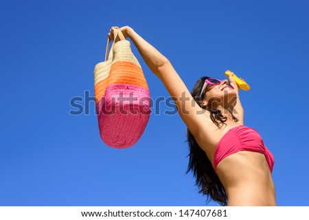 Happy summer vacation. Blissful bikini woman ready for sunbathing protecting skin with sunscreen or suntan lotion. Sexy caucasian girl raising arms to clear blue sky enjoying summertime, heat and sun.