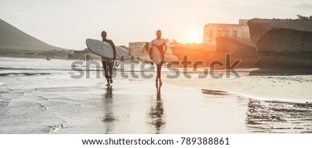 Happy surfers couple running with surf boards on the beach - Sporty people having fun in surfing day - Extreme sport and vacation concept - Main focus on man body and board #789388861
