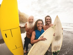 Happy surfers having fun taking selfie with action camera - Young multigeneration people doing surf during vacation - Family and extreme sport concept - Soft focus on faces