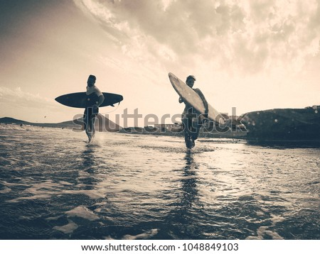Happy surfers running with surf boards on the beach - Sporty people having fun in sunny day - Extreme sport, travel, vacation concept - Focus on left male silhouette - Black and white vintage editing