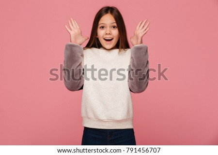 Happy surprised beautiful brunette girl in casual clothes looking camera and smiling isolated over pink