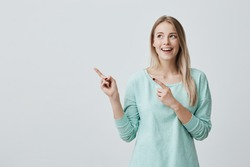 Happy surprised blonde young female smiling broadly at camera, pointing fingers away, showing something interesting and exciting on studio wall with copy space for your text or advertising content