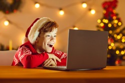 Happy surprised child looking at laptop computer screen lighting up his face, seeing wonderful Christmas gifts and amazing presents in Internet store or watching online Xmas film on cinema website