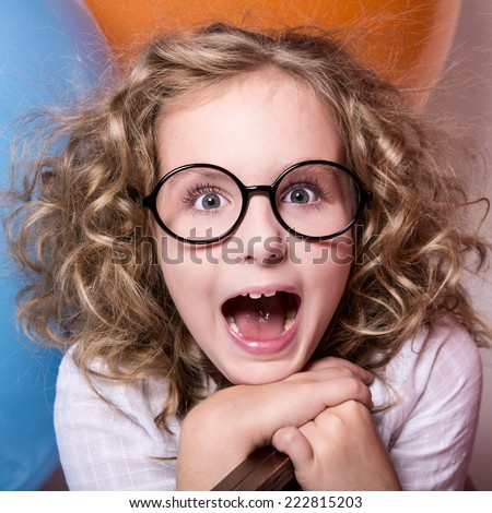Happy surprised girl in glasses with an open mouth on a background of large balloons. square photo