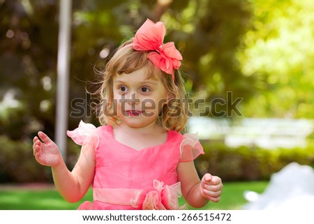 Happy surprised little beautiful girl in pink dress