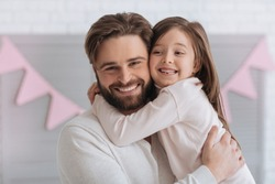 Happy sweet girl hugging her father