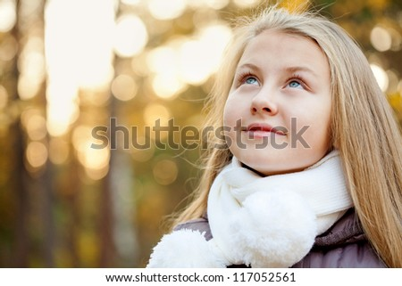 Happy sweet young girl in autumn clothes  looking up
