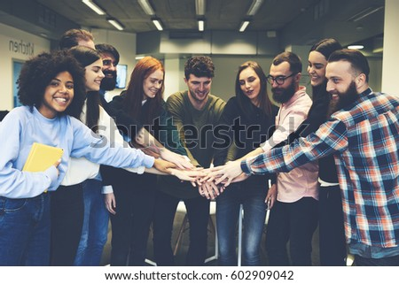 Happy talented team male and female members feeling exciting finishing good job setting up successful startup project increase income to company giving high five greeting each other with victory