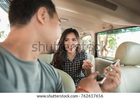 happy taxi driver showing mobile phone to his customer - Shutterstock ID 762617656