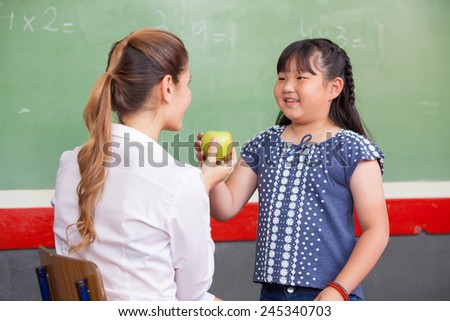 Happy teacher and asian elementary female student touching a green apple.