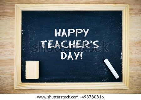 Happy Teacher's Day.. Blackboard with Happy Teacher's Day sign, white chalk and duster on wooden background #493780816