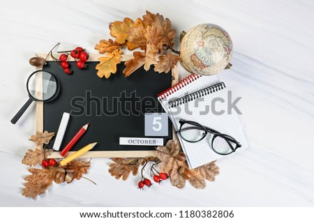 Happy teacher\'s day. Teachers day, 5 october concept.  the school blackboard and Glasses teacher books and pencils on the table, on the background of a blackboard with chalk.