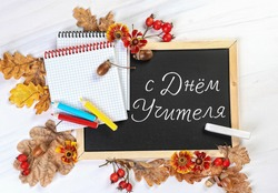 Happy teacher's day - text translation Russian language. Teachers day greeting card concept. autumn leaves, books and stationery on school blackboard.