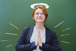 Happy teacher with a halo drawn over his head prays at the blackboard. Holy woman teacher at school