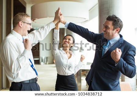 Happy team giving hi-five after successful work #1034838712