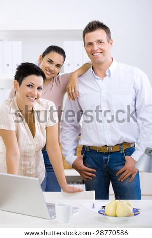 Happy team of office workers running small business, smiling.