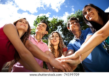 Happy team of people with hands together outdoors