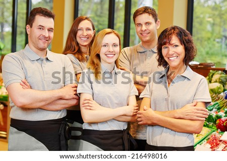 Happy team of smiling men and women staff in a supermarket