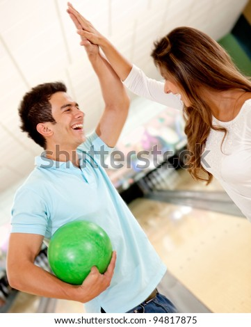 Happy team winning at bowling and giving a high-five