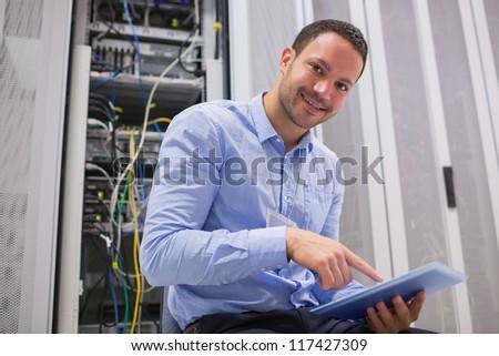 Happy technician working on tablet pc beside servers in data center