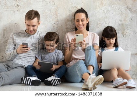 Happy technology addicted family parents and kids use laptop phone digital tablet sit on floor at home, mom dad with children obsessed with devices overuse social media, internet addiction concept