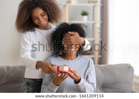 Happy teen african american girl closing mum eyes make surprise to excited black mommy giving birthday gift box congratulating mixed race mom with mothers day holding present sitting on sofa at home