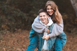 Happy teen boy and girl 15-16 year old having fun outdoors over autumn nature background. Looking at camera. Happiness.