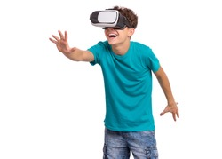 Happy teen boy wearing virtual reality goggles watching movies or playing video games. Cheerful smiling teenager looking in VR glasses. Funny child experiencing 3D gadget technology.