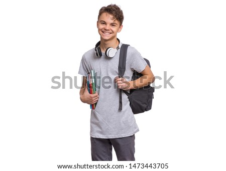 Happy teen boy with headphones and backpack holding books, isolated on white background. Smiling child looking at camera. Emotional portrait of handsome teenager guy Back to school. stock photo