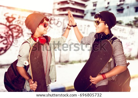 Happy teen boys outdoors, two stylish teenagers with skateboards in hands saluting each other, modern lifestyle, hipster culture, active summer holidays