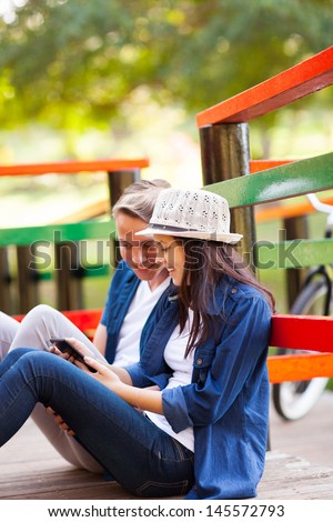 happy teen couple using tablet computer sitting on the bridge outdoors
