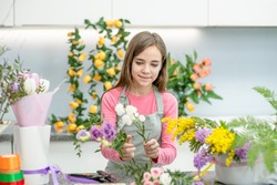 Happy teen girl arranging flower at flower shop. Hobby and leisure concept