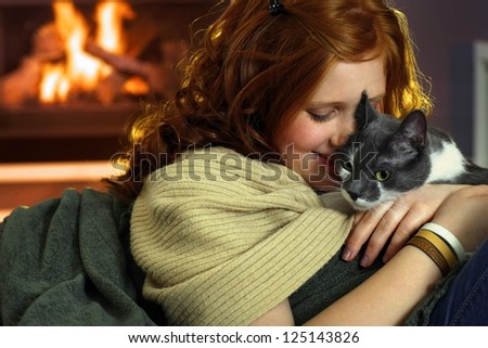 Happy teen girl caressing cat at home, affectionate moment.