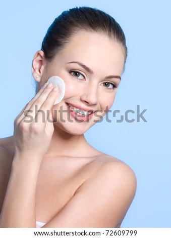 Happy teen girl caring about her fresh healthy skin of face with cotton swab disk - blue background