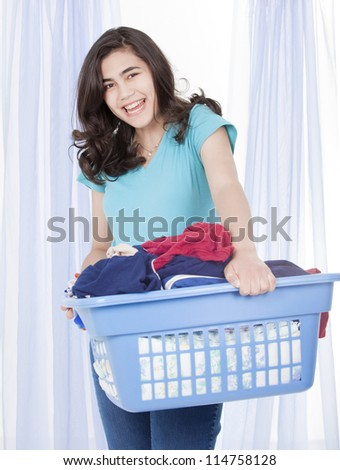 Happy teen girl doing the laundry, carrying a load of clothes in basket