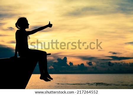 happy teen girl sitting on beach at the dawn time