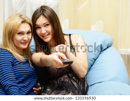 Happy teen girl watching tv together with her mother on sofa at home