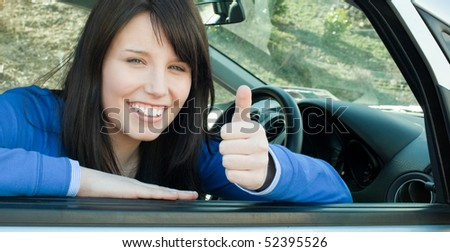 Happy teen girl with a thumb up sitting in her car after having her driver's licence
