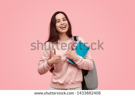 Happy teen girl with backpack and notebooks smiling and showing thumb up gesture while approving education against pink background