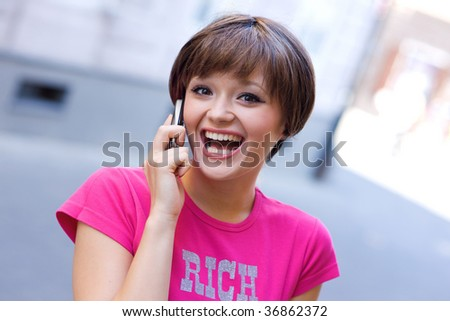 happy teen girl with mobile phone on the street