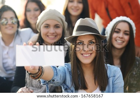 Happy teen girls having good fun time outdoors with banner paper for copy space